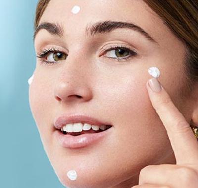 mujer aplicandose crema suero en el rostro en puntos especificos con fondo blanco